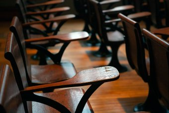 wooden desks with arm tables in a classroom