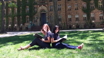 Two students hanging out outside Nassau Hall Front Lawn